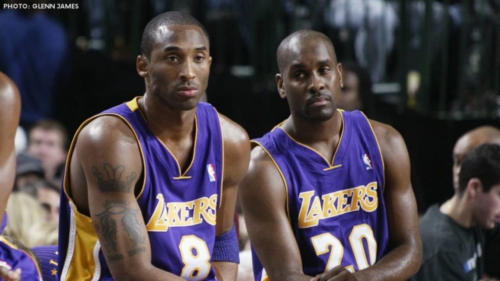 Gary Payton and Kobe Bryant in Lakers uniform, sitting at the bench.